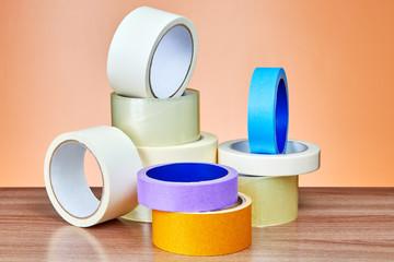 Multi colored multipurpose adhesive tape rolls lie on table.