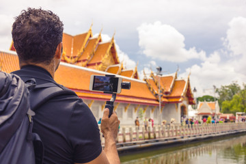 Autocollant pour porte Cracovie Man backpacher who holds mobile phone on gimbal visiting Asia during a sunny day , Solo trip , holiday and vacations concept .
