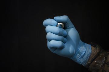 Tattoo artist holding a tattoo machine on dark background in studio.
