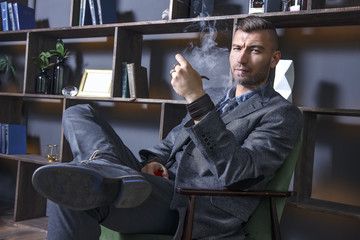 elegant man in suit sits in chair and smokes pipe. handsome stylish rich brutal man in luxurious apartment. Serious view of successful businessman. Clubs of smoke from a cigar in a dark interior.
