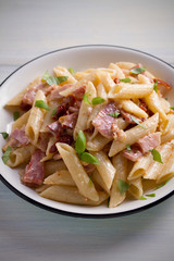 Penne pasta with bacon and sundried tomatoes. Alfredo penne pasta on white plate on wooden table. vertical