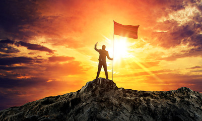 Businessman with flag on mountain top. Concept for success.