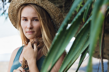 Young beautiful hipster woman in straw hat hold in hands bouquet of dried wild flowers. Happy romantic girl walk on tropical sea beach. Travel lifestyle, summer vacation accessories trend - boho style