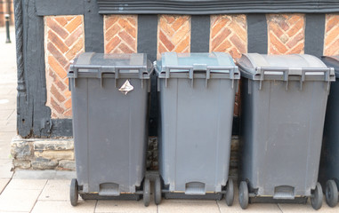 wheelie bins against Tudor wall in UK tourist town Stratford upon Avon awaiting collection