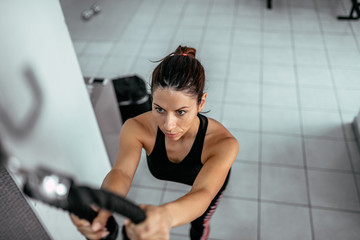 High view angle image of woman exercising on pull down machine at gym.