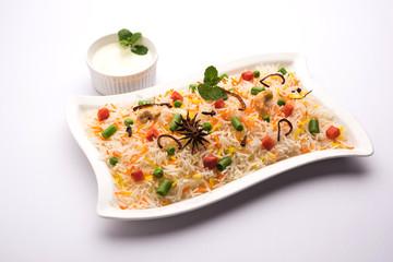Indian Vegetable Pulav or Biryani made using Basmati Rice, served in a ceramic bowl. selective focus