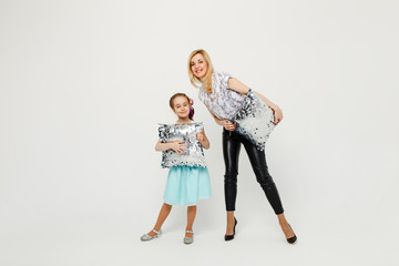 happy beautiful mother and daughter in full length on a white background