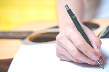 male composer hands writing a song on white paper