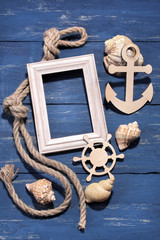Marine attributes. Rope, frame, wooden anchor and steering wheel on a blue wooden background. Top view