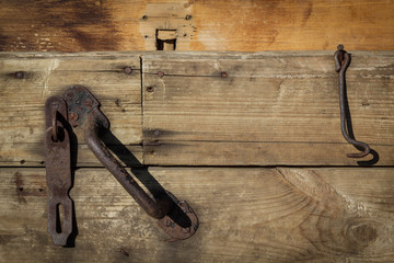 Old wooden weathered door of boards with iron handle