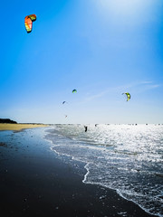 Kite surfer on the ocean beach. Silhouette of kite surfer across the sea shore. Outdoor Active Lifestyle.