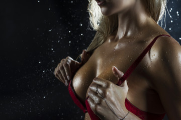 Close Up photo of wet hot and sweaty sensual big tits of tanned athletic blonde girl wearing red bra under falling water drops of rain on black.