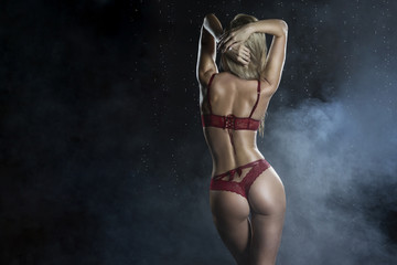 Beautiful wet sporty big tits tanned blonde girl wearing red underwear posing from the back in scenic smoke and fog under falling water drops of rain on black.