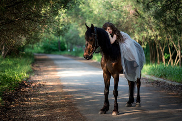 beautiful girl in a smart dress fell on a horse