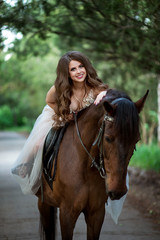 beautiful girl in elegant dress sits on horseback and smiles
