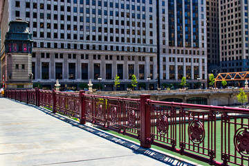 Shadows on the LaSalle Street bridge over a green Chicago River in spring.