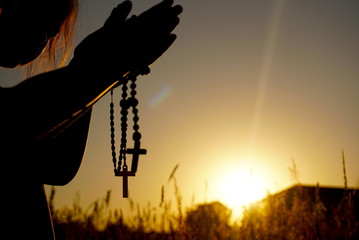 children pray on rosaries at sunset