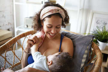 Motherhood, infantry, parenting and childhood concept. Picture of cheerful young brunette Hispanic woman wearing headscarf smiling broadly, nursing her infant child in cozy bedroom interior