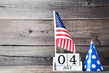 American flag with cube calendar and paper cap on wooden table