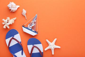 Flip flops with seashells and decorative ship on orange background