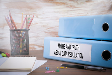 Myths and truth about data regulation, General Data Protection Regulation, GDPR concept. Office Binder on Wooden Desk. On the table colored pencils, pen, notebook paper