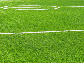 White stripe on the green soccer field from side view. Artificial turf on football field. Green synthetic grass on sport ground with white lines