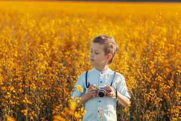 Portrait of little boy photographer with camera on sunset yellow field background