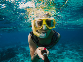 Lovely woman doing snorkeling at the gili islands in Indonesia. Wearing yellow glasses at the blue sea. Travel photography, lifestyle.