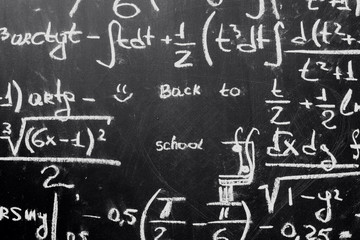 Back to school background with math formulas are written by white chalk on the black chalkboard