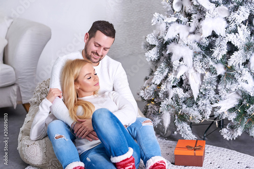 A Beautiful Happy Young Couple Sitting On The Ground And Hugging Each Other With Christmas