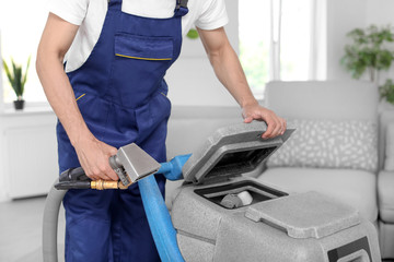 Dry cleaning worker with professional apparatus indoors