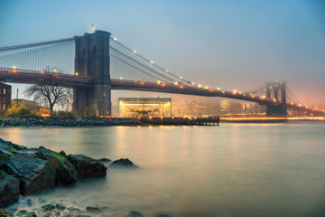 Fototapete - Brooklyn bridge and Manhattan at foggy evening, New York City