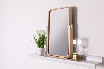 Shelf with modern mirror on white wall