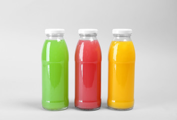 Bottles with delicious colorful juices on light background