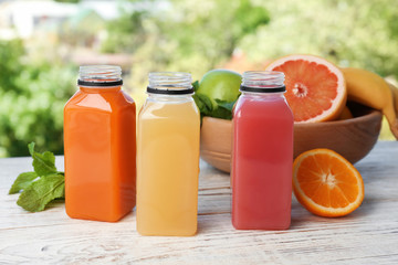 Bottles with tasty juices and ingredients on table