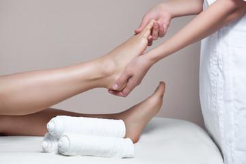 The cosmetologist wraps the leg