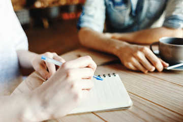Hands of woman making notes in her notepad while discussing business ideas with her male partner over coffee in cafe