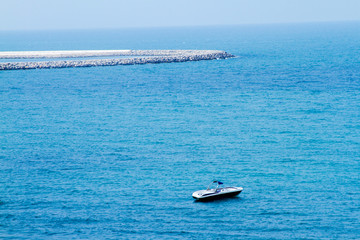 Beautiful blue sea and boats and beach resort huts from al hamra beach view