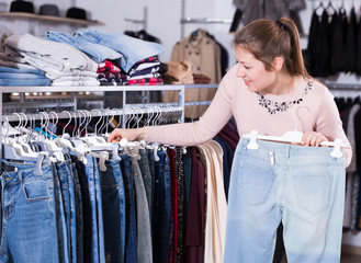 Cheerful young woman choosing stylish jeans