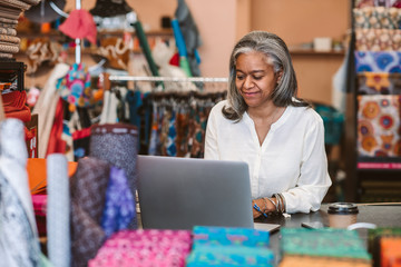 Smiling mature woman using a laptop in her fabric shop
