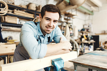 Portrait of cheerful handsome furniture maker leaning on wood plank in his workshop and smiling at camera