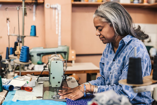 Mature woman using a sewing machine in her fabric workshop