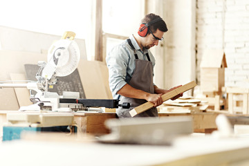 Young carpenter wearing protective eyeglasses and earmuffs preparing to saw wood plank with electric circular saw. Wall mural