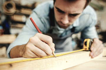 Concentrated professional carpenter measuring wood plank and making mark with pencil.
