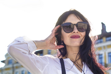 Portrait of a happy and joyful young woman on a blue sky background. Successful feminine in sunglasses.