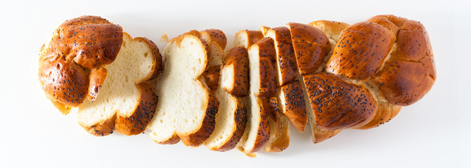 banner cut braided bread sprinkled with poppy seeds, isolated on white. copy space