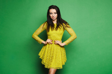 Beautiful, sexy and fashionable brunette model girl with blue eyes and bright makeup, in short yellow dress and sunglasses on her head posing at green background
