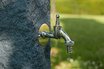 Silver faucet at a stone