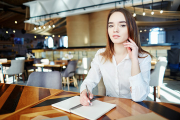 Portrait of beautiful young businesswoman looking at camera while sitting at table in cafe and making notes in her notebook
