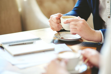 Unrecognizable businessman having coffee at meeting with defocused business partner; documents, notebook and pen on table